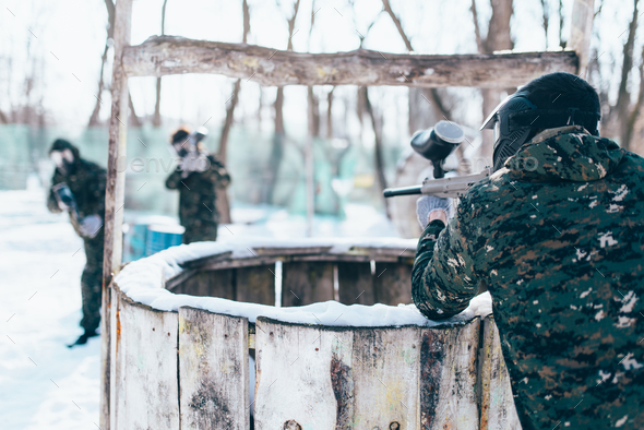 Paintball player shooting at the enemy team - Stock Photo - Images