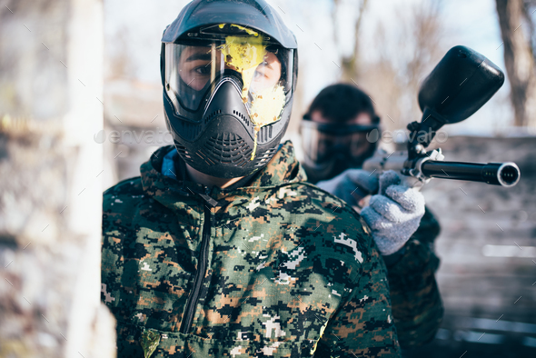 Paintball player in splattered mask, front view - Stock Photo - Images