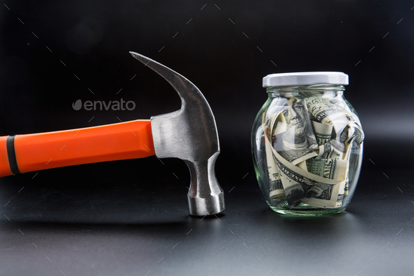 Hammer against jar full of dollars, money saving - Stock Photo - Images