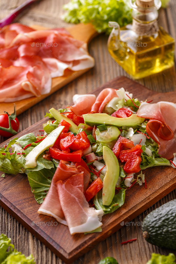 Green salad with thin slices of ham - Stock Photo - Images