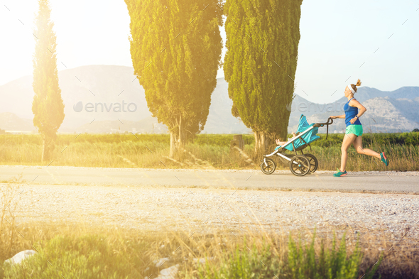 Running mother with stroller enjoying motherhood at sunset lands - Stock Photo - Images