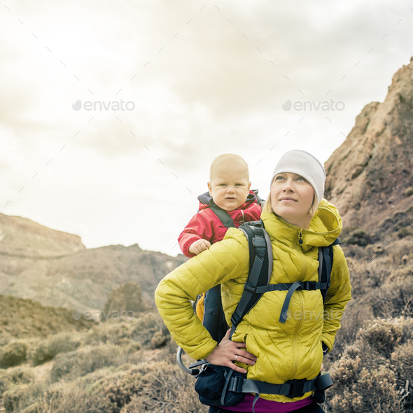 Superhero mother with little boy travelling in backpack - Stock Photo - Images