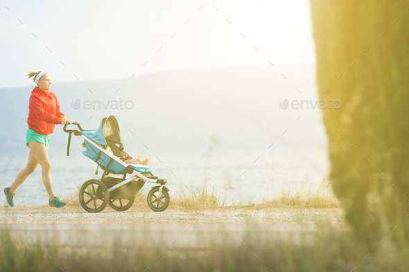 Running mother with baby stroller enjoying sunset landscape - Stock Photo - Images