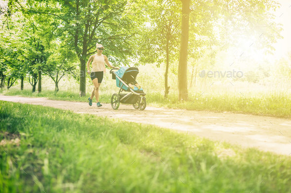 Running woman with baby stroller enjoying summer in park - Stock Photo - Images