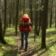 The Woman with a Red Backpack Travels Around the Forest Road. Scandinavian Walking - VideoHive Item for Sale