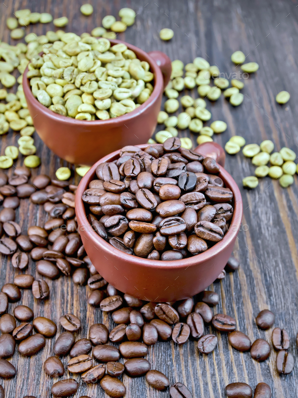 Coffee black and green grains in cups on board - Stock Photo - Images