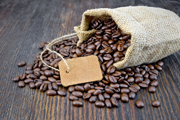 Coffee black grain with tag in bag on board - Stock Photo - Images