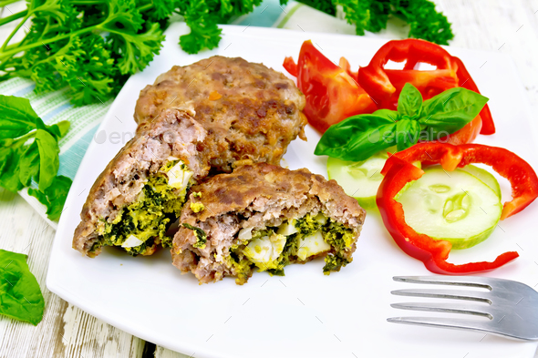 Cutlets stuffed with vegetables in plate on board - Stock Photo - Images