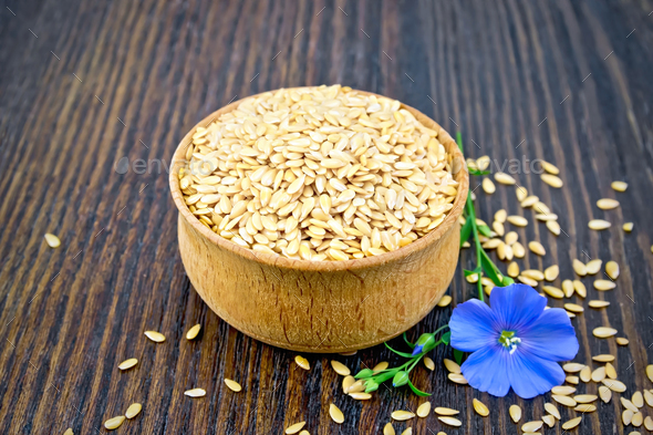 Flaxen white seed in bowl with blue flower on board - Stock Photo - Images