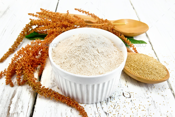 Flour amaranth in bowl with spoon and flower on board - Stock Photo - Images