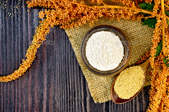 Flour amaranth in bowl with spoon and flower on board top - Stock Photo - Images