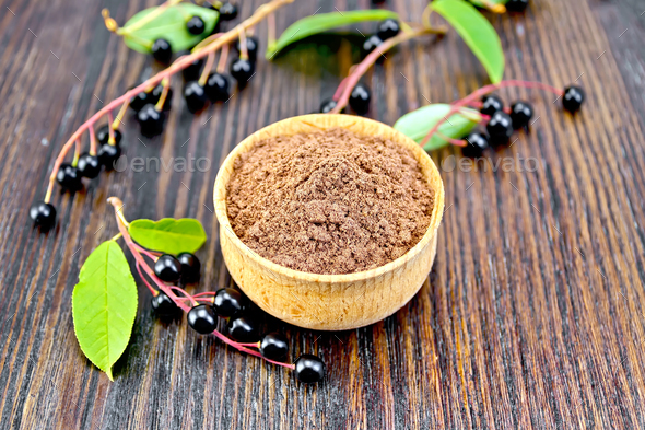 Flour bird cherry in bowl with berries and leaves on board - Stock Photo - Images