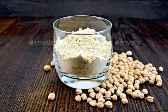 Flour chickpeas in glassful on dark board - Stock Photo - Images