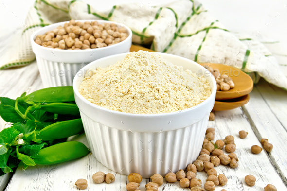 Flour chickpeas in white bowl on light board - Stock Photo - Images