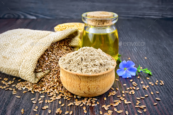 Flour linen in bowl with oil and flower on board - Stock Photo - Images