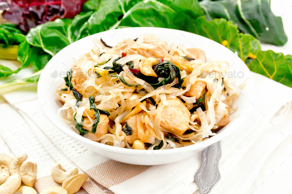 Funchoza with chard and cashew in bowl on light board - Stock Photo - Images