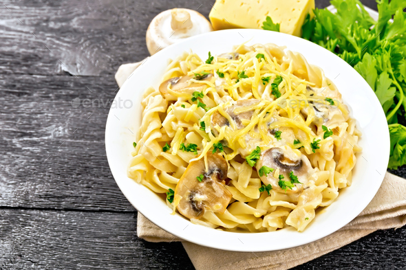 Fusilli with mushrooms and cream in plate on board - Stock Photo - Images