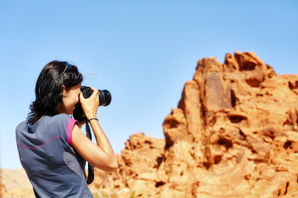 Female fit photographer takes pictures of rock formations. - Stock Photo - Images