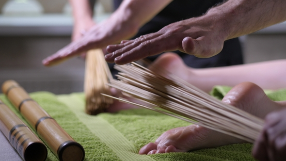 Two Male Masseurs Working with Woman  Japanese Feet Massage with Bamboo  Sticks in the Spa Salon