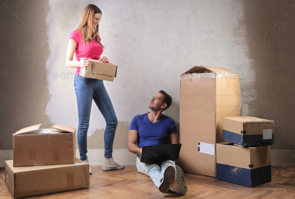 Couple with boxes in a new house - Stock Photo - Images