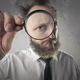 Man looking trough a magnifying glass - PhotoDune Item for Sale
