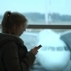 Female Traveler Waiting for Departure and Using Her Cellphone. a Young Girl Writes a Message - VideoHive Item for Sale