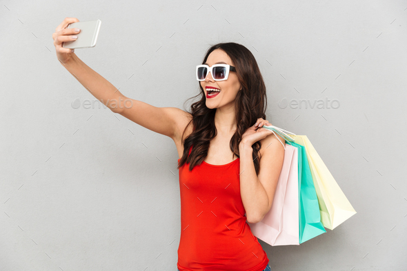 Cheerful brunette woman in casual clothes and sunglasses making selfie - Stock Photo - Images