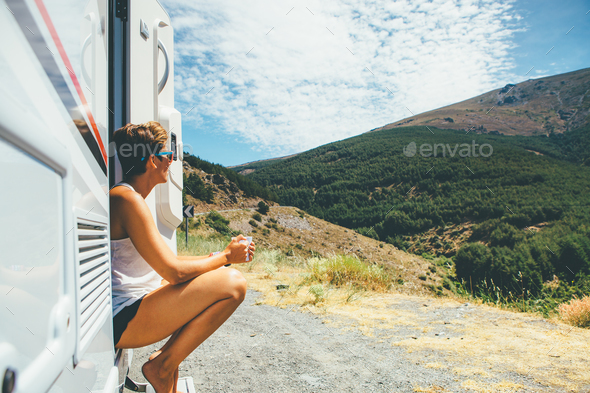 Girl sits on a motor home step - Stock Photo - Images