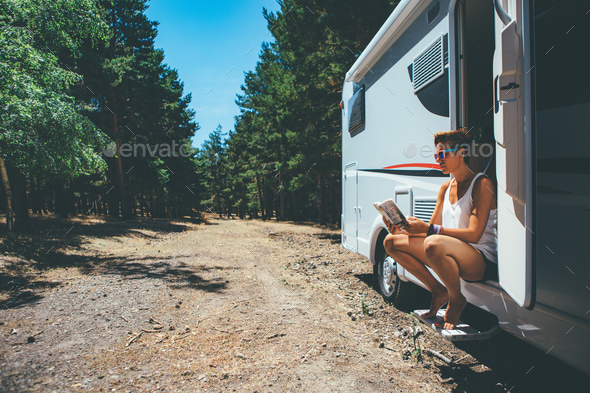 Girl reads on a motor home door step - Stock Photo - Images