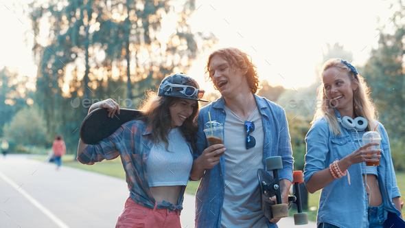 Happy young friends with skateboards - Stock Photo - Images