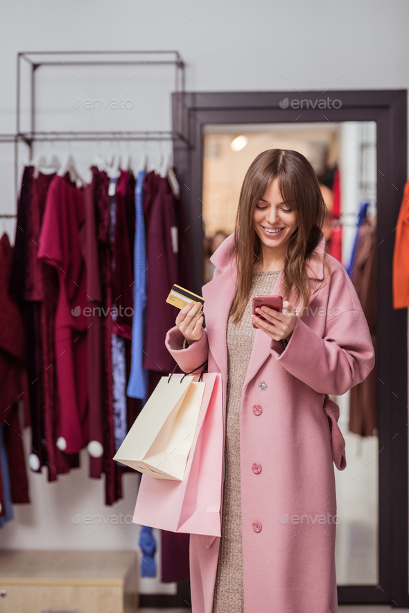 Smiling young customer with a credit card - Stock Photo - Images