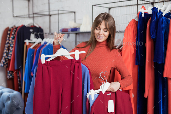 Smiling girl with hangers indoors - Stock Photo - Images