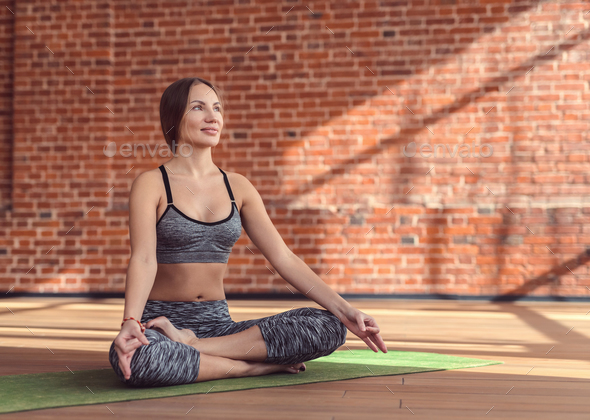 Young girl in a lotus position indoors - Stock Photo - Images