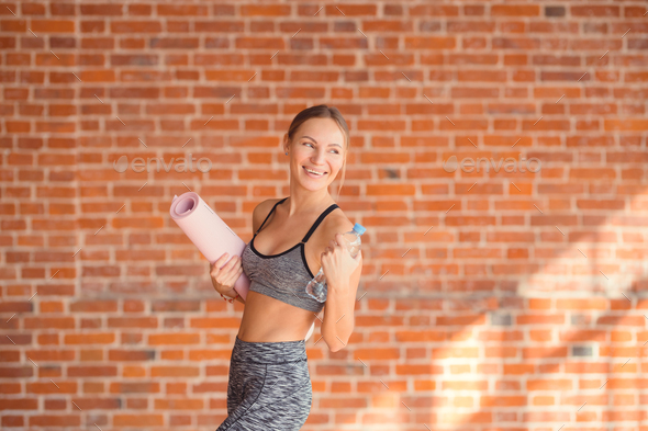Smiling young girl with a mat - Stock Photo - Images