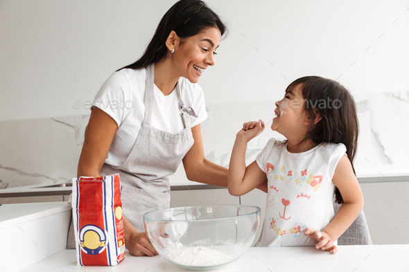 Young mother in apron cooking and baking with her smiling little - Stock Photo - Images