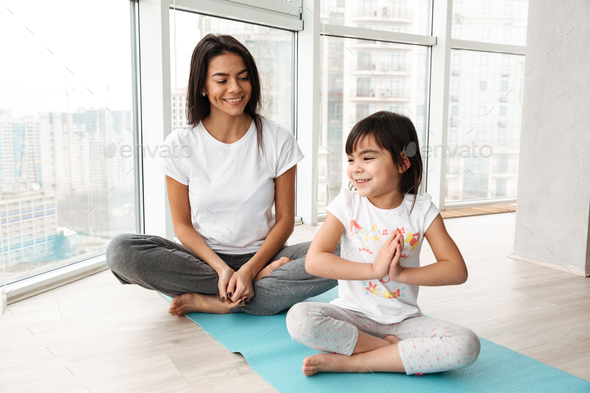 Happy people woman and little kid practicing yoga indoor, sittin - Stock Photo - Images