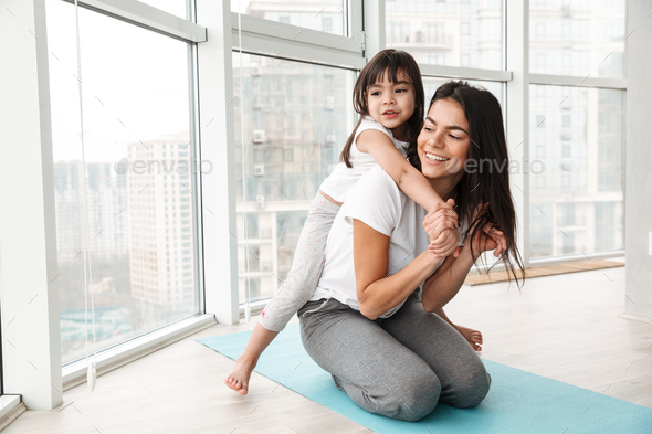 Photo of caucasian young woman and her girl kid playing around, - Stock Photo - Images
