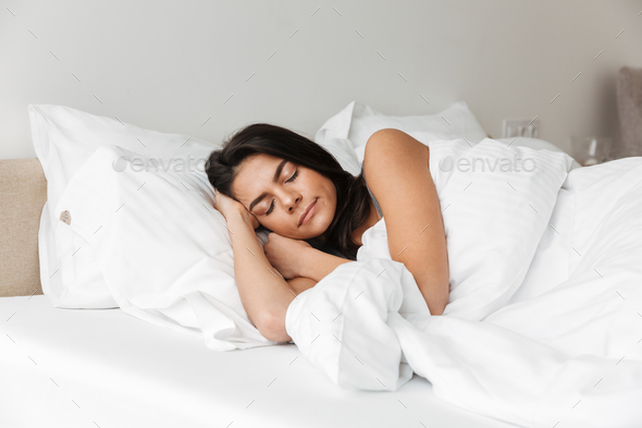 Portrait of brunette woman sleeping at home in bed on pillow, wi - Stock Photo - Images