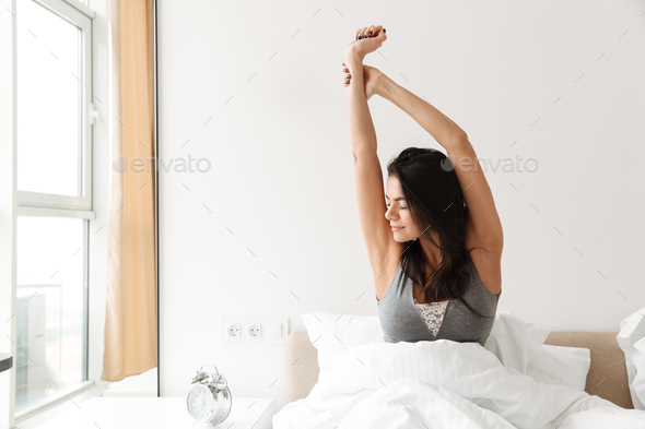 Portrait of lovely morning woman stretching after sleep, while r - Stock Photo - Images