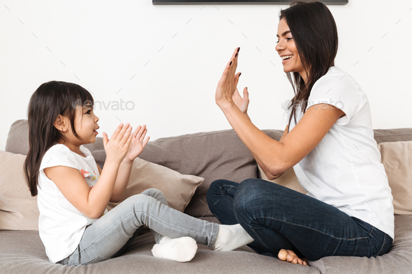 Portrait of cheerful family mother and girl playing together pat - Stock Photo - Images