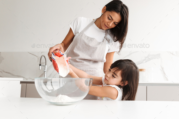 Young mother wearing apron cooking pastry with her little daught - Stock Photo - Images