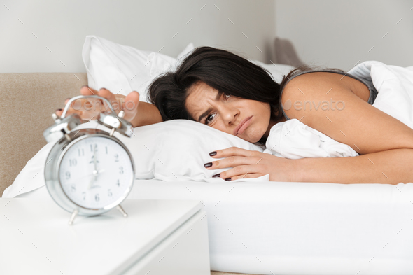 Image of dissatisfied woman 20s lying in bed on pillow, and turn - Stock Photo - Images