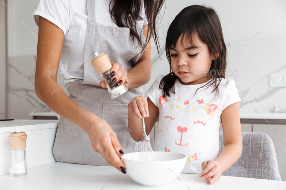 Photo closeup of housewife in apron with her little daughter coo - Stock Photo - Images