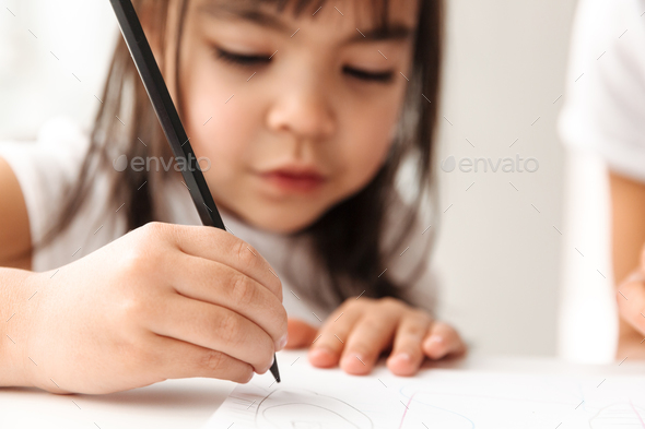 Portrait closeup of brunette girl 7y in defocus drawing painting - Stock Photo - Images