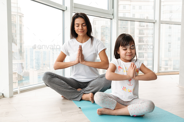Beautiful mother and child meditating at home, sitting legs cros - Stock Photo - Images