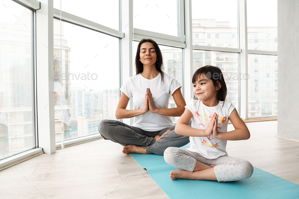 Relaxed people woman and kid practicing yoga indoor, sitting leg - Stock Photo - Images