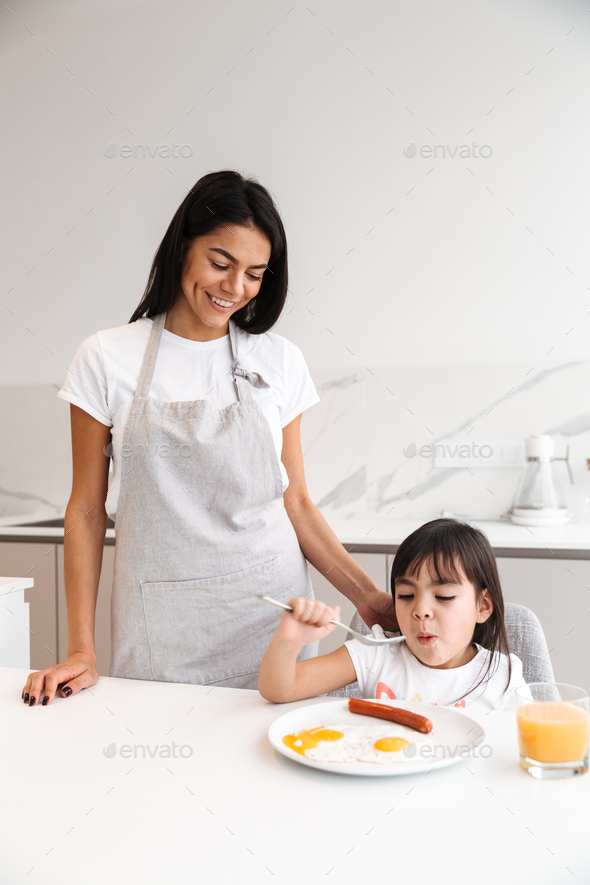 Beautiful happy woman in apron standing in kichen and making bre - Stock Photo - Images