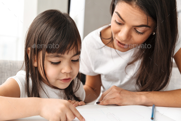 Image of lovely mother and little daughter enjoying painting tog - Stock Photo - Images