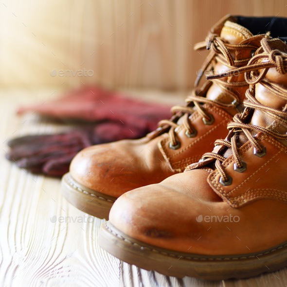Yellow leather used work boots and protective gloves on wooden b - Stock Photo - Images
