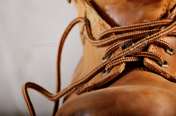 Yellow leather used work boots on concrete background closeup. P - Stock Photo - Images